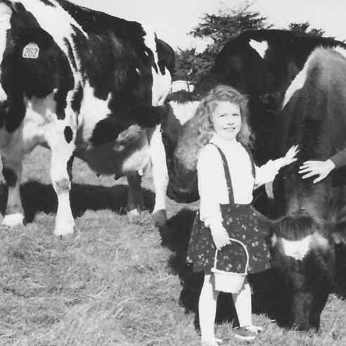 young Marissa with her grandpa's dairy cows